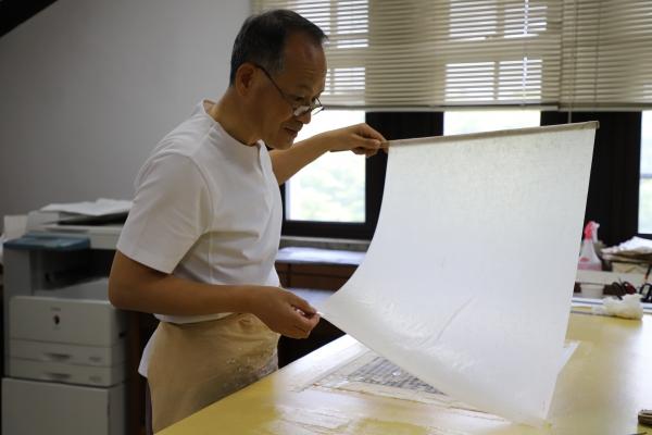보존처리가 박상호 씨가 배접지를 덧대고 있다.